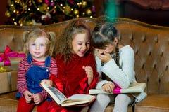 Santa Claus och grupp av flickor som läser en bok Royaltyfria Foton