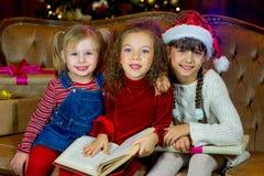 Santa Claus och grupp av flickor som läser en bok Arkivbild