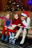Santa Claus och grupp av flickor som läser en bok Royaltyfria Bilder
