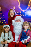 Santa Claus och grupp av flickor som läser en bok Royaltyfri Foto