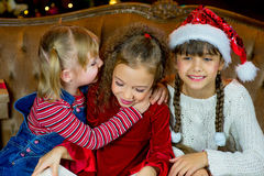 Santa Claus och grupp av flickor som läser en bok Fotografering för Bildbyråer