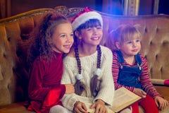 Santa Claus och grupp av flickor som läser en bok Royaltyfri Fotografi