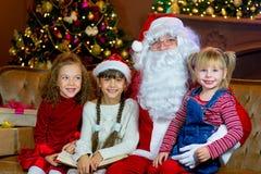 Santa Claus och grupp av flickor som läser en bok Royaltyfri Bild