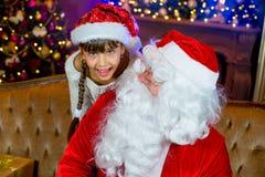 Santa Claus och lettleflicka med julgåvor Royaltyfri Foto