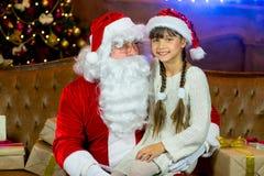 Santa Claus och lettleflicka med julgåvor Royaltyfria Bilder