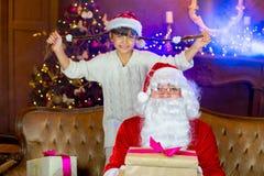Santa Claus och lettleflicka med julgåvor Arkivbild