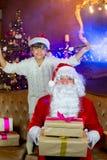Santa Claus och lettleflicka med julgåvor Royaltyfri Fotografi
