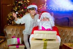 Santa Claus och lettleflicka med julgåvor Fotografering för Bildbyråer