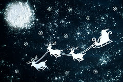Santa Claus och renflyg till och med natthimlen Arkivbilder