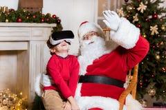 Santa Claus och unge i vrhörlurar med mikrofon arkivbild