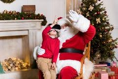 Santa Claus och unge i vrhörlurar med mikrofon fotografering för bildbyråer