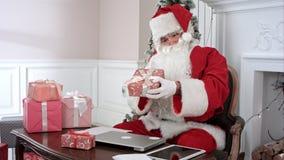 Santa Claus ocupada que prepara presentes usando el ordenador portátil y la tableta digital, clasificando sus letras y recibiendo fotografía de archivo libre de regalías