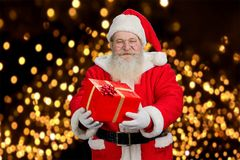 Santa Claus offering beautiful gift box. Stock Images