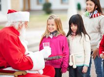 Santa Claus Offering Biscuits And Milk To Children Royalty Free Stock Images