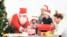Santa Claus offering Christmas present to the mother Royalty Free Stock Photography