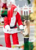 Santa Claus Offering Cookies To Girl Royalty Free Stock Photography
