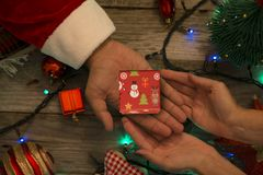 Santa Claus offering a small gift box to a happy woman on a festive Christmas decor stock photos