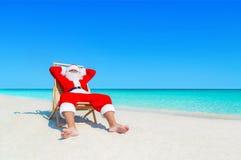 Santa Claus ontspant in sunlounger bij zandig tropisch overzees strand stock foto