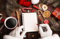 Santa Claus with open notepad. On wooden table stock images