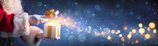 Free Santa Claus Opening Christmas Present With Golden Stars Stock Images - 163173074