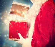 Santa Claus Opening ein großes Weihnachtsgeschenk stockbild