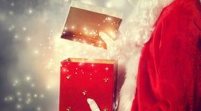 Santa Claus Opening ein rotes Weihnachtsgeschenk Lizenzfreie Stockbilder