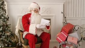 Santa Claus opening an envelope and reading a letter. Professional shot on Lumix GH4 in 4K resolution. You can use it e.g. in your commercial video, business Royalty Free Stock Photos