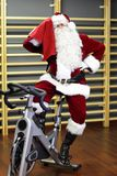 Santa Claus-opleiding op hometrainers bij de gymnastiek royalty-vrije stock fotografie