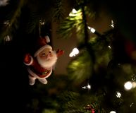 Santa Claus Ornament Hanging From A Fully Lit Christmas Tree Royalty Free Stock Image
