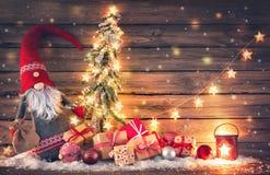 Santa Claus ou o anão guardam uma árvore de abeto com surr das luzes de Natal fotos de stock