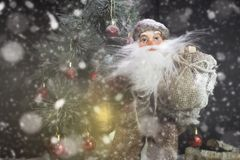 Santa Claus Outdoors Beside Christmas Tree beim Schneefall-Tragen Lizenzfreies Stockfoto
