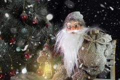 Santa Claus Outdoors Beside Christmas Tree beim Schneefall-Tragen Lizenzfreie Stockfotos