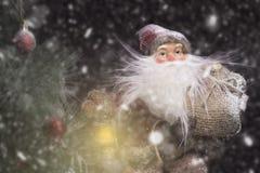 Santa Claus Outdoors Beside Christmas Tree beim Schneefall-Tragen Lizenzfreie Stockbilder
