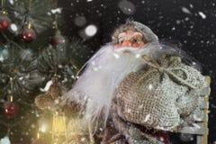 Santa Claus Outdoors Beside Christmas Tree dans le transport de chutes de neige Photographie stock