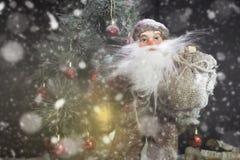Santa Claus Outdoors Beside Christmas Tree em levar da queda de neve Foto de Stock Royalty Free