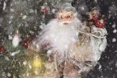 Santa Claus Outdoors Beside Christmas Tree em levar da queda de neve Fotografia de Stock Royalty Free