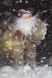 Santa Claus Outdoors Beside Christmas Tree em levar da queda de neve Fotos de Stock Royalty Free
