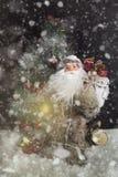 Santa Claus Outdoors Beside Christmas Tree, i att bära för snöfall Arkivbild