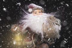 Santa Claus Outdoors Beside Christmas Tree, i att bära för snöfall Fotografering för Bildbyråer