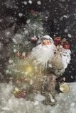 Santa Claus Outdoors Beside Christmas Tree in Sneeuwval het Dragen Stock Fotografie