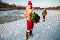 Santa Claus på en cykel med ett dragspel Royaltyfri Fotografi