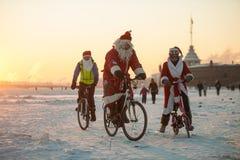 Santa Claus på en cykel med ett dragspel Arkivbild