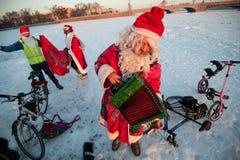 Santa Claus på en cykel med ett dragspel Royaltyfri Foto