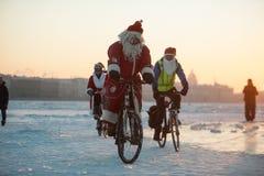 Santa Claus på en cykel med ett dragspel Arkivfoto