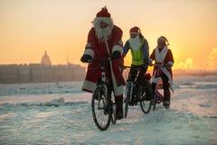 Santa Claus på en cykel med ett dragspel Arkivfoton