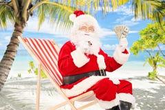 Santa Claus på en semester och att sitta på stol med cigarren och oss för att göra Arkivfoto