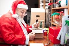 Santa Claus packing a gift Stock Photo
