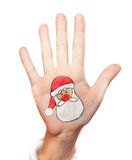 Santa Claus painted on kid's hand Stock Photography