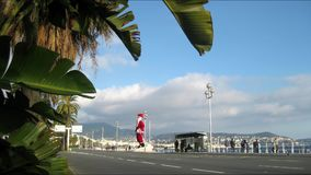 Santa Claus and palm trees in Nice on a windy day. Timelapse of a statue of Santa Claus on the beach of Nice, France, on a windy day. 11 December, 2016 stock video footage