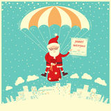 Santa Claus on parachute fly in winter sky. Stock Photo